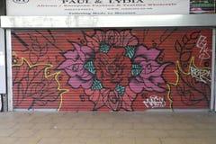 Graffiti auf einem closedup Shop im Verminderungseinkaufssäulengang St George `` gehen in Croydon lizenzfreie stockfotos