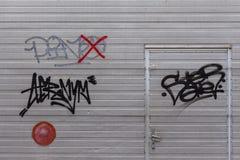 Graffiti auf Metallgaragetür stockbilder