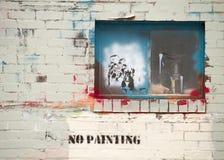 Graffiti behandelde muur en venster taunting zaken Stock Foto