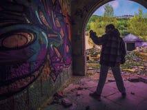 Graffiti boy. Boy finishing a graffiti on a wall of an abandoned hospital Royalty Free Stock Images