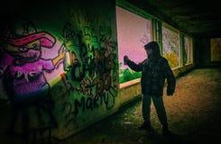 Graffiti boy II. Boy finishing a graffiti on a wall of an abandoned hospital Royalty Free Stock Image