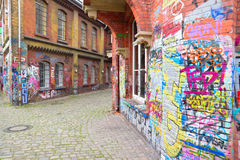 Graffiti brick wall art scale alley in germany Royalty Free Stock Photo