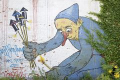 Graffiti on brick wall, Doel, Belgium. Graffiti painting -depicting red nosed man in blue clothes lighting fire crackers- on white wall of abandoned house in stock illustration
