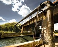 Graffiti bridge. Bridge and pipeline over river with graffiti royalty free stock images