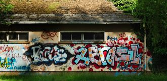 Graffiti. A building hidden under trees with a lot of graffiti royalty free stock photos