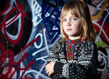 Graffiti child cool street art. Child in front of graffiti wall in urban area. Cool young boy by street art in deprived town area Royalty Free Stock Photo