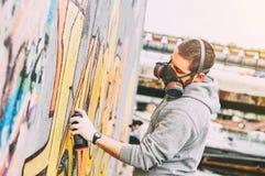 Graffiti coloré de peinture d'artiste de rue sur un mur sous le pont - homme urbain exécutant avec des murales - concept d'art mo photo stock