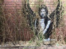 Graffiti d'un ange à ailes derrière le feuillage photo stock