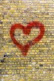 Graffiti de coeur sur un fond jaune de mur de briques Image stock