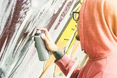 Graffiti de peinture d'artiste de rue avec la couleur pulv?riser son art sur le mur - murales de inscription et de dessin de jeun photos stock
