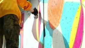 Graffiti del disegno del giovane sulla parete con la latta di spruzzo archivi video