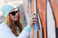 Graffiti del disegno dell'adolescente con la pittura di spruzzo fotografia stock