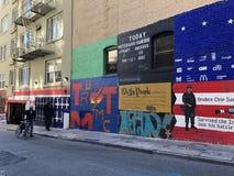Graffiti del muro di cinta Camminata della gente fotografia stock