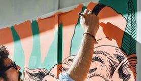 Graffiti del ragazzo, dipingenti la parete, con la penna Fotografia Stock