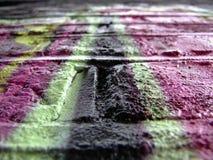 Graffiti detail. Pink & black bricks royalty free stock photography