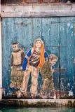Graffiti die drie jongens op een houten deur van een oude buildi afbeelden Royalty-vrije Stock Fotografie