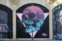Graffiti, die eine Wand entlang einer Straße verzieren stockfotografie