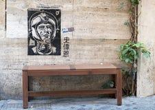 Graffiti, die einen Raumfahrer auf Wand über einer Bank auf einer Straße in Rom zeigen stockbild