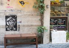 Graffiti, die einen Raumfahrer auf Wand über einer Bank auf einer Straße in Rom zeigen lizenzfreie stockbilder