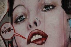 Graffiti die het gezicht van een jonge vrouw afschilderen Stock Foto