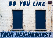 Graffiti Do you like your neigbours on yellowing brick wall. Graffiti of slogan `Do you like your neighbours` in blue block capital stencil on yellowing white Royalty Free Stock Photos