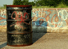 Graffiti Drum. An oil drum and barrier sitting on a roadside, vandalized with graffiti stock photos