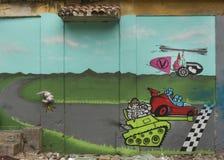 Graffiti eines Rennens zwischen Behälter, Auto und Hubschrauber Lizenzfreie Stockfotos