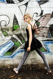Graffiti Fairy. Black costume fairy lady with wings standing next to a graffiti wall Stock Photo