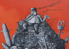 Graffiti: fat capitalist sitting on a heap of corporate junk. Royalty Free Stock Image