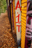 Graffiti on fence. Graffiti on a brightly coloured fence in a park, with a path leading into the distance Royalty Free Stock Images