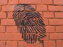 Graffiti-Fingerabdruck auf einer Backsteinmauer Stockbilder