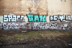 Graffiti fragment with colorful text on old yellow wall Stock Images