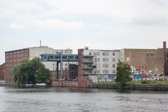 Graffiti-geschilderde baksteengebouwen dichtbij Fuifrivier in Kreuzberg, Berlijn stock fotografie