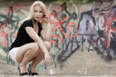 Graffiti Girl. A pretty blonde teenager in front of a wall covered in graffiti Royalty Free Stock Photography
