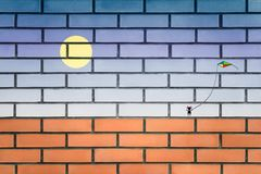 Graffiti the girl walking with a kite on a brick wall royalty free stock photos