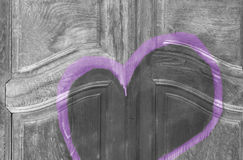 Graffiti heart. On a wooden door in monochrome colors, leaving a symbolic message on a grungy doorstep royalty free stock photos