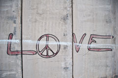 Graffiti on Israeli Separation Barrier. Graffiti on the Israeli separation barrier says, Love with a peace sign as the letter o Stock Image