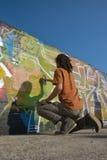 Graffiti-Künstler bei der Arbeit über eine neue Schaffung Lizenzfreie Stockbilder
