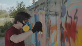 Graffiti master with respirator painting on street wall. 4K.  stock video footage
