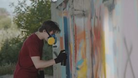 Graffiti master with respirator painting on street wall. 4K.  stock footage