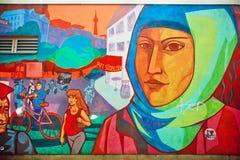 Graffiti met gezicht van vrouw in hijab die op gebied van immigranten leven royalty-vrije stock afbeelding