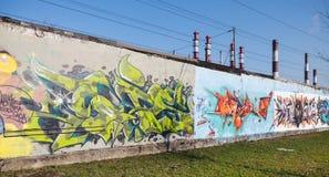 Graffiti mit Mustern und Text auf alten grauen Betonmauern Stockfoto