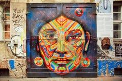 Graffiti mit schönem Gesicht ethnischer Dame auf der rustikalen Tür Stockfotografie
