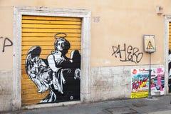 Graffiti mit Schwarzweiss-Engel auf gelbem Tor Stockfoto