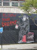 Follow your dreams by Mr Brainwash. London, UK. Graffiti by Mr Brainwash on a boarded up building in London showing a monkey holding a pot of paint beside a royalty free stock image
