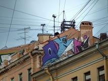Graffiti na dachu stary dom z drutami i antenami Zdjęcie Royalty Free