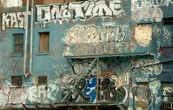 Graffiti on a NYC Building. Brick wall of an abandonned warehouse covered with graffiti is a prime example of inner city blight with its free-style tags left by Stock Images