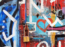 Vibrant graffity on old door with lock.