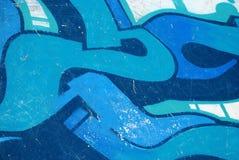 Graffiti op blauwe de krasachtergrond van de skateparkmuur Stock Foto