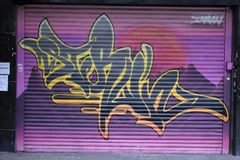 Graffiti op een closedupwinkel in de verlaging het winkelen arcadest George `` Gang in Croydon Stock Foto's